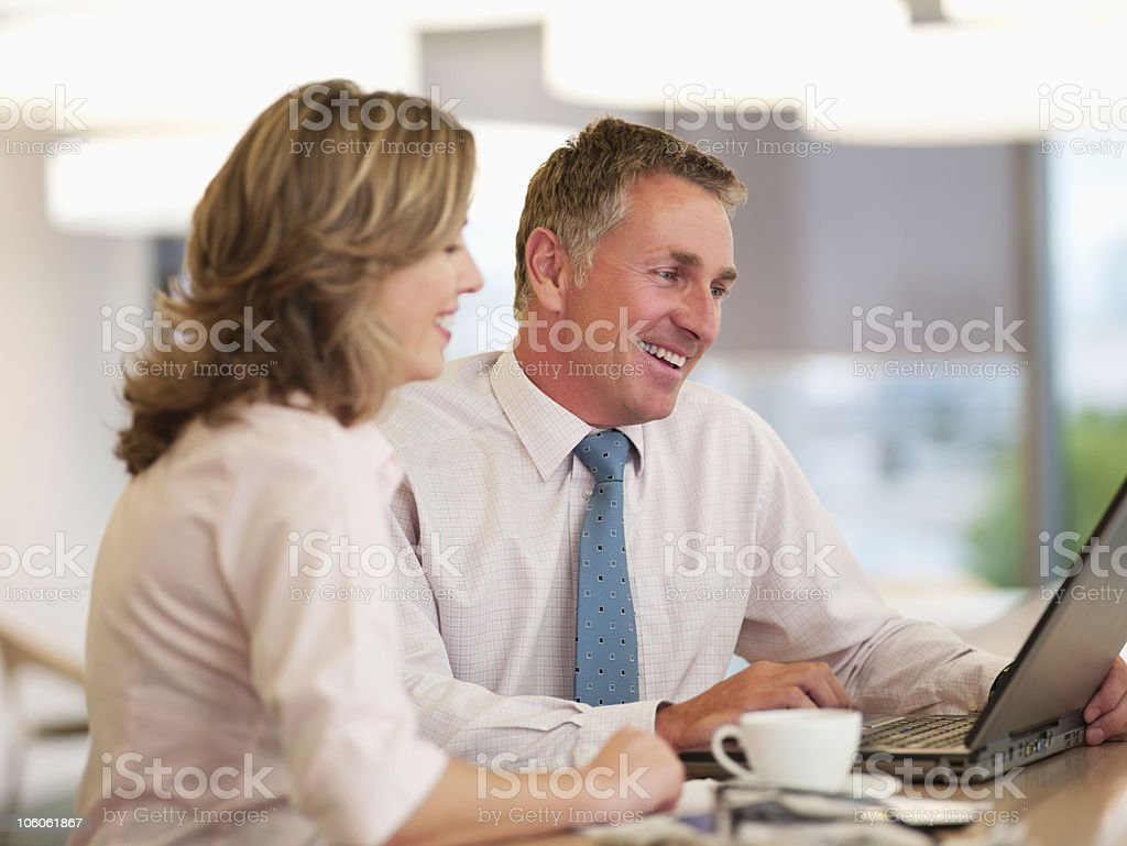 Businessman and woman using laptop together royalty-free stock photo