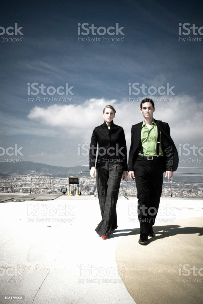 Businessman and Woman Walking off Helicopter Pad stock photo