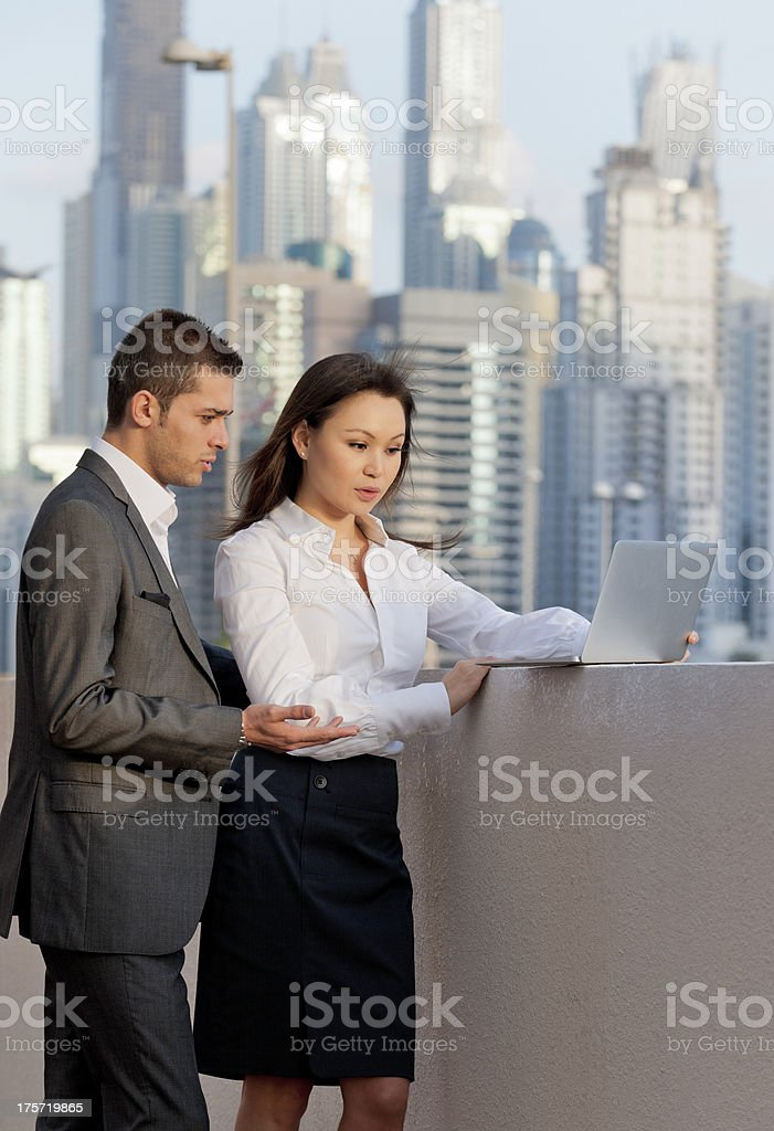 businessman and woman working on laptop in downtown district stock photo