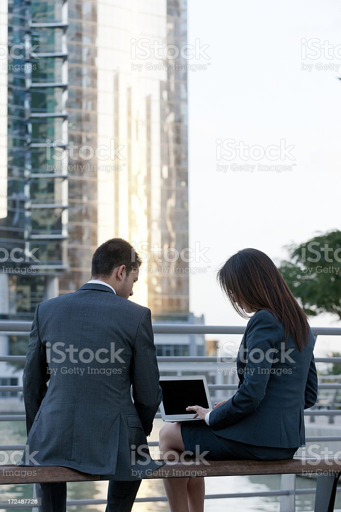 businessman and woman working on laptop in financial district stock photo