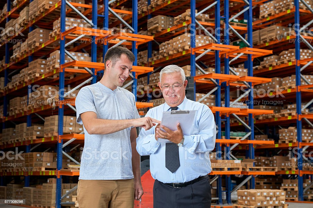 Businessman and worker checking checklist in warehouse stock photo