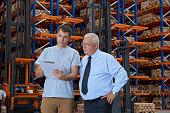 Businessman and worker checking checklist in warehouse