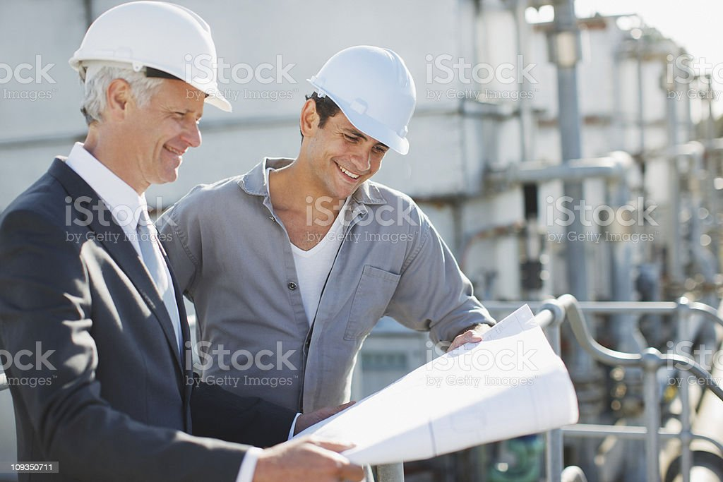 Businessman and worker reviewing blueprints outdoors royalty-free stock photo