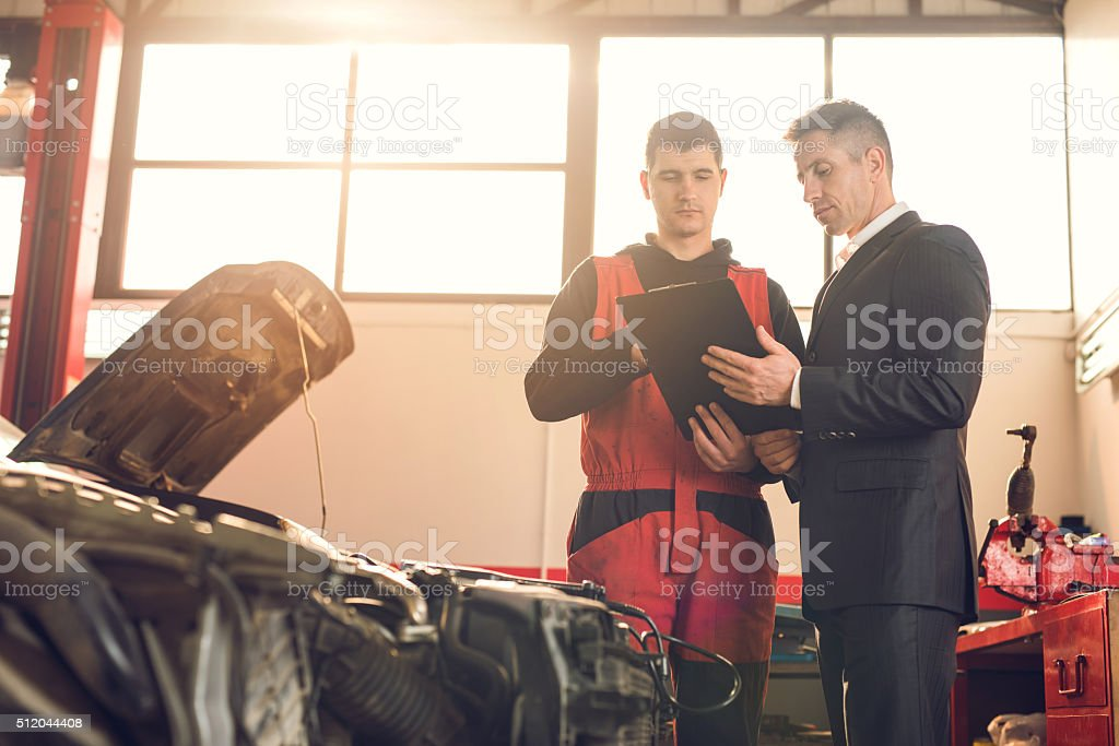 Businessman and young mechanic going through paperwork in repair shop. stock photo