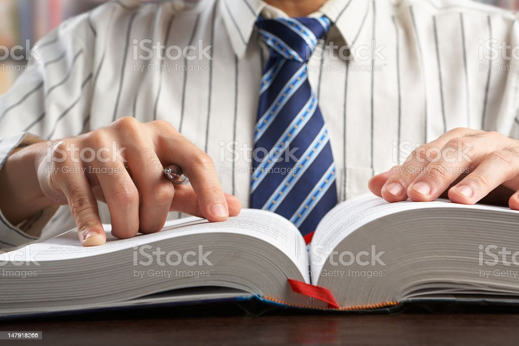 Businessman and/or professor reading a textbook stock photo