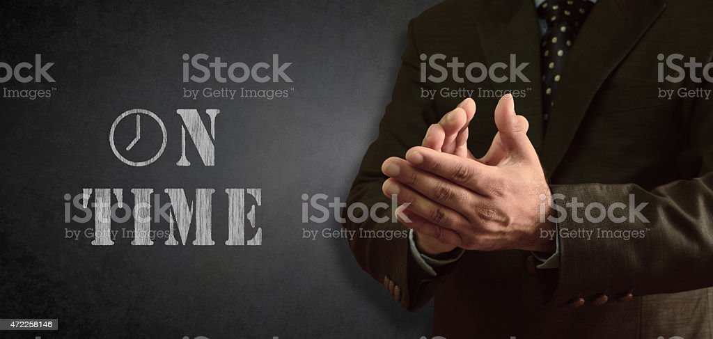 Businessman appreciating On Time delivery - blackboad in background stock photo