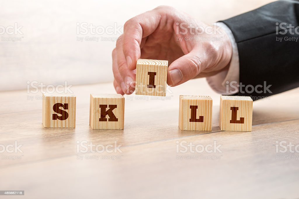 Businessman Arranging Blocks to Form Skill Word stock photo