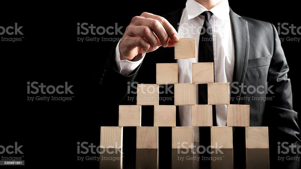 Businessman Arranging Wooden Blocks to Pyramid stock photo
