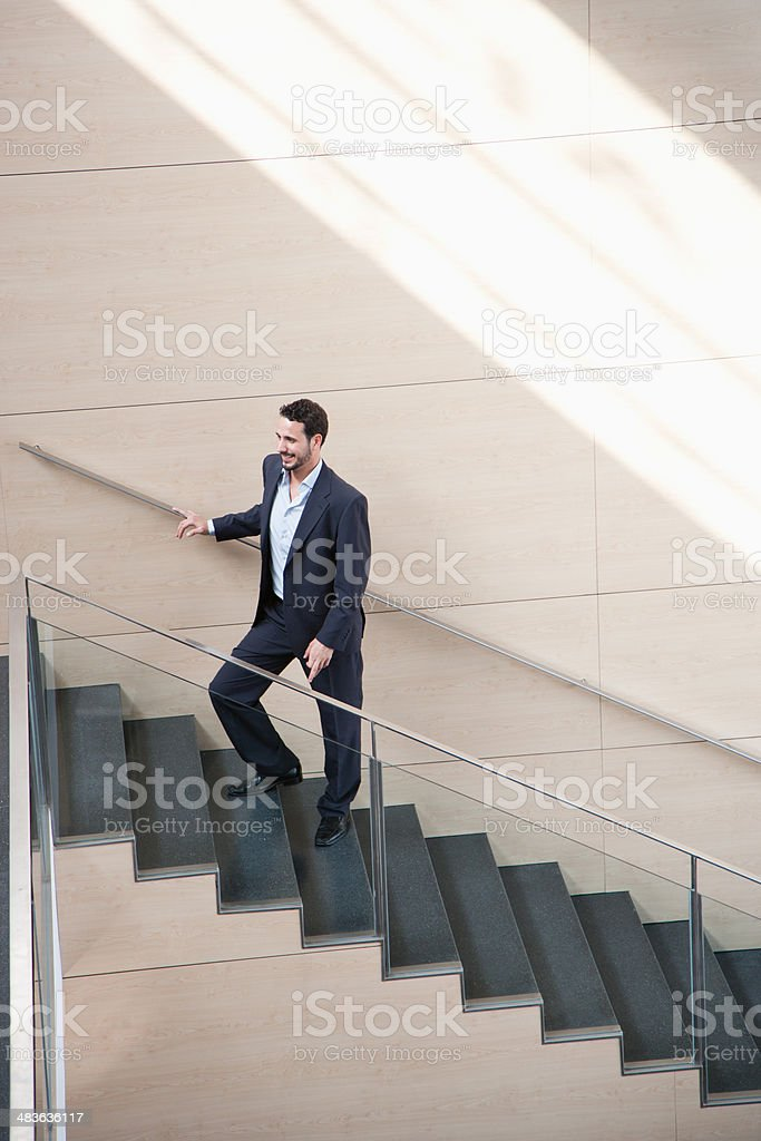 Businessman ascending office staircase stock photo