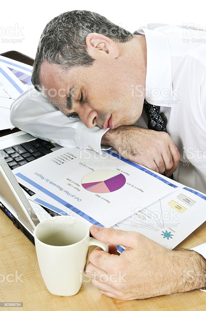 A businessman asleep at his desk with business charts royalty-free stock photo