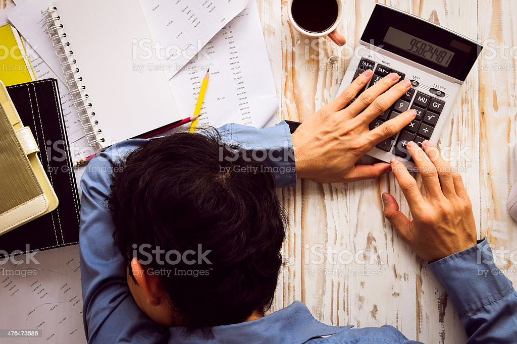 Businessman asleep at office desk with finance sheet stock photo