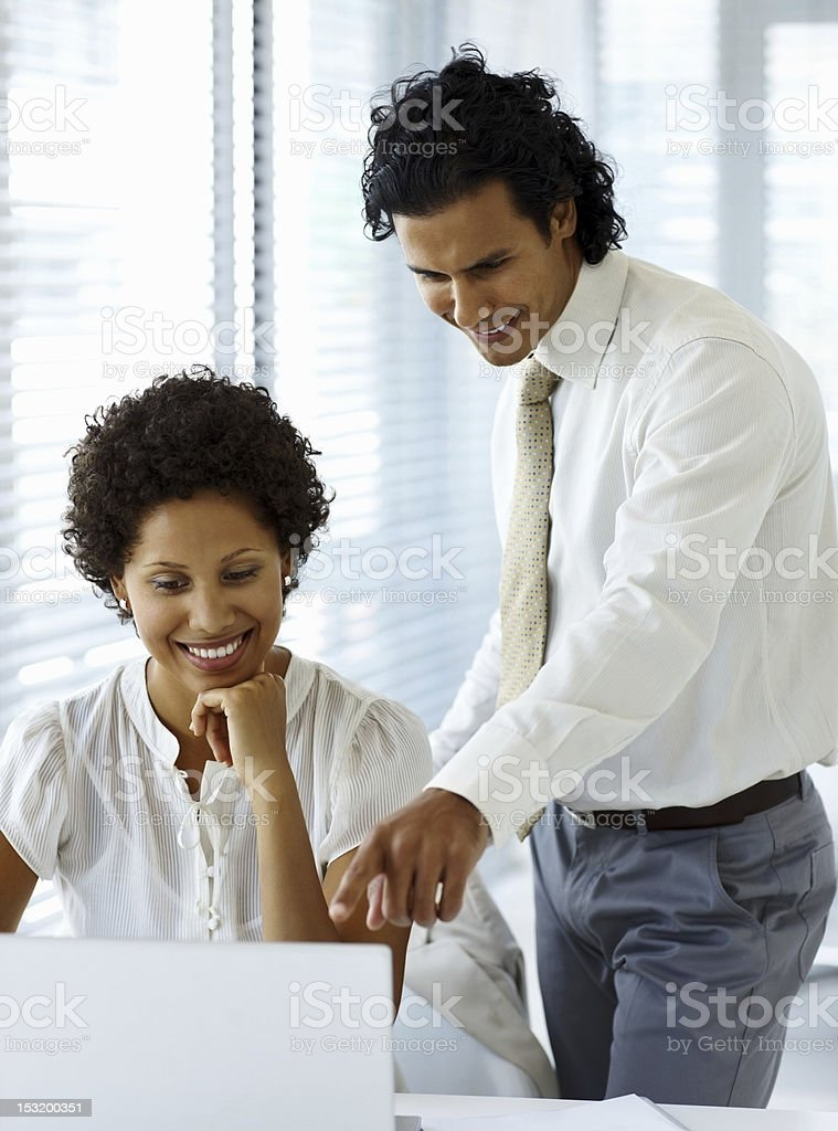 Businessman assisting his colleague and smiling at work royalty-free stock photo