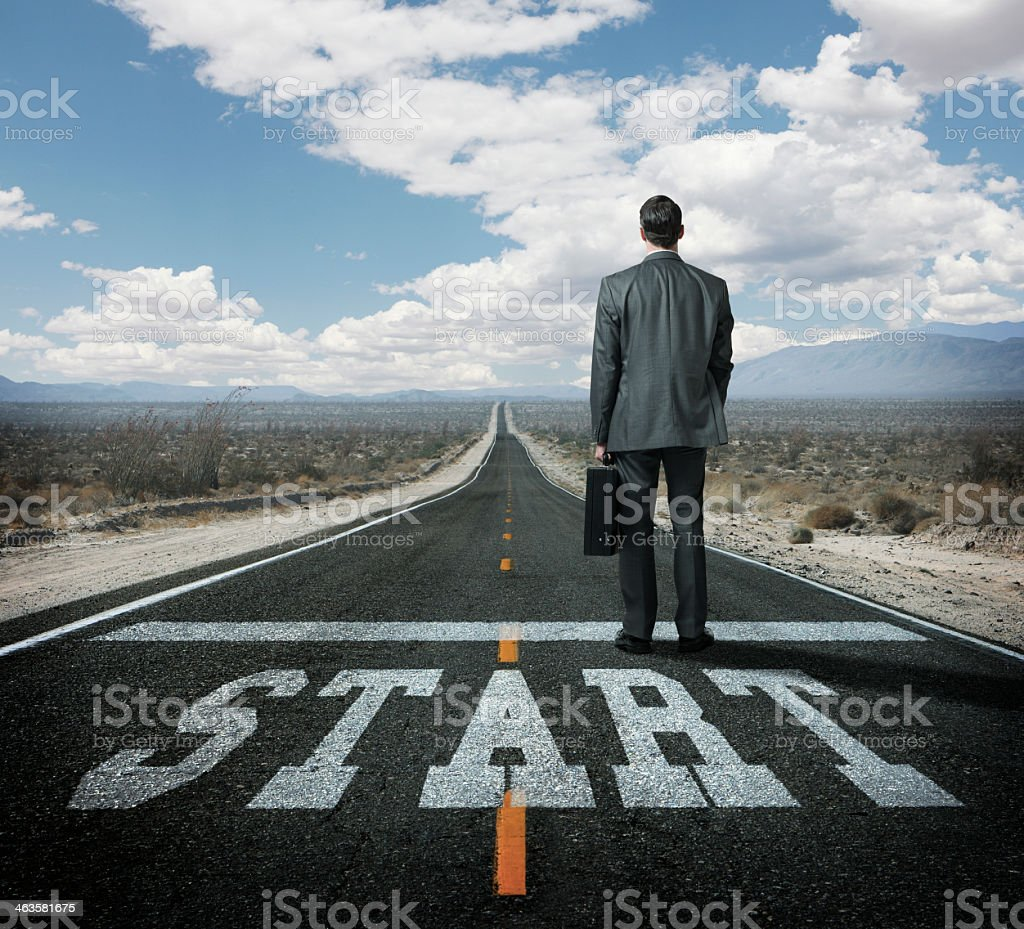 Businessman at a starting line on long desert highway stock photo