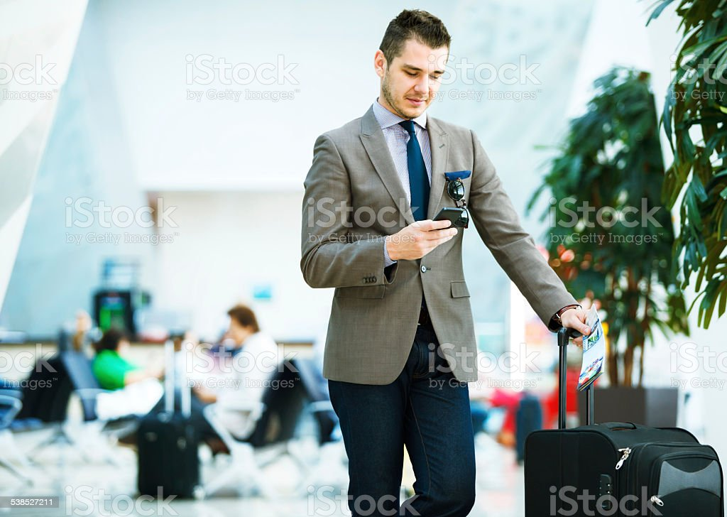 Businessman at airport with smartphone and suitcase stock photo