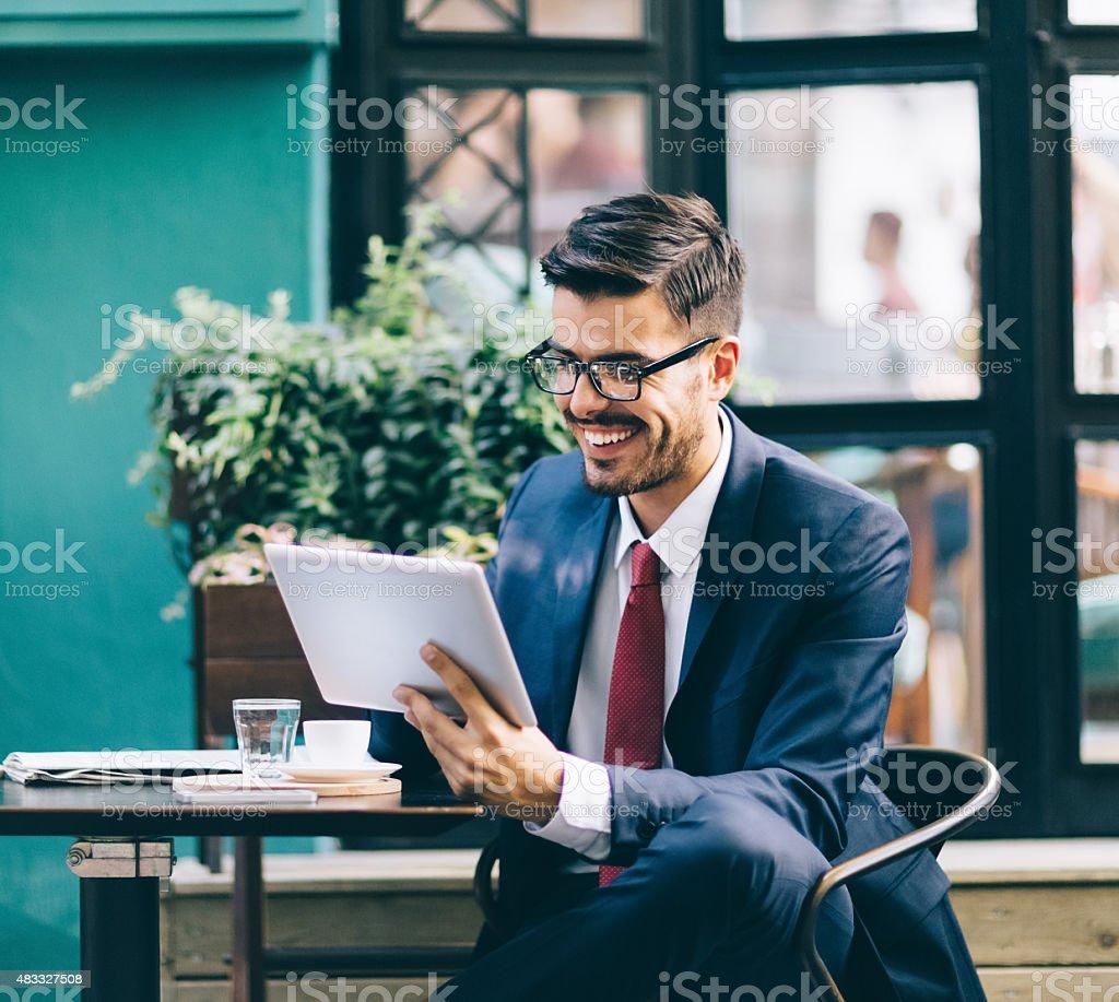 Businessman at coffee break using tablet stock photo