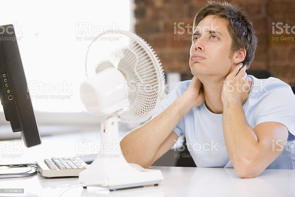 Businessman at desk with fan and laptop stock photo