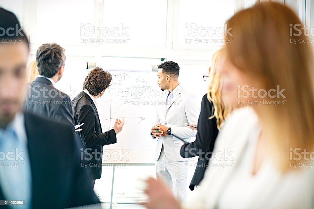 Businessman at flip chart talking to colleagues stock photo