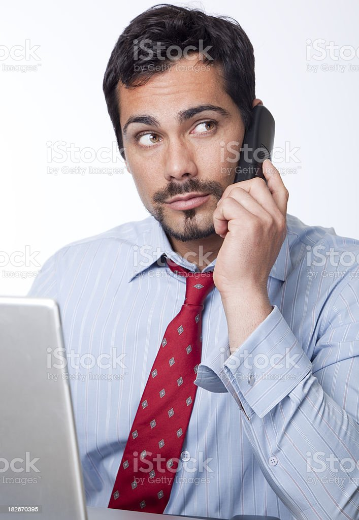 businessman at his desk on the phone stock photo