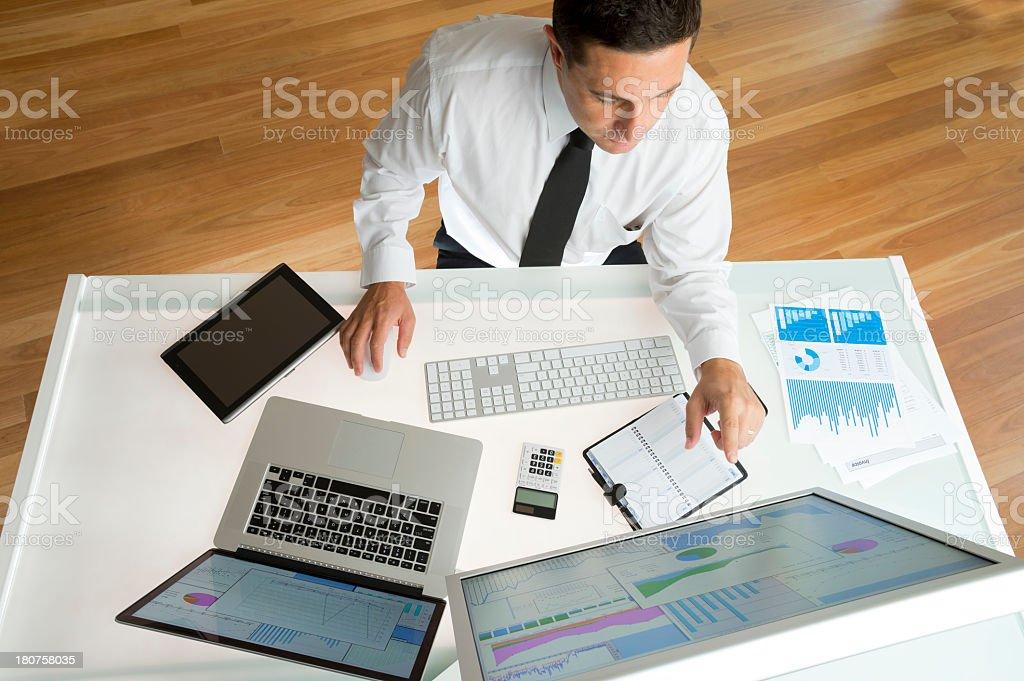 Businessman at his desk viewing stock charts royalty-free stock photo