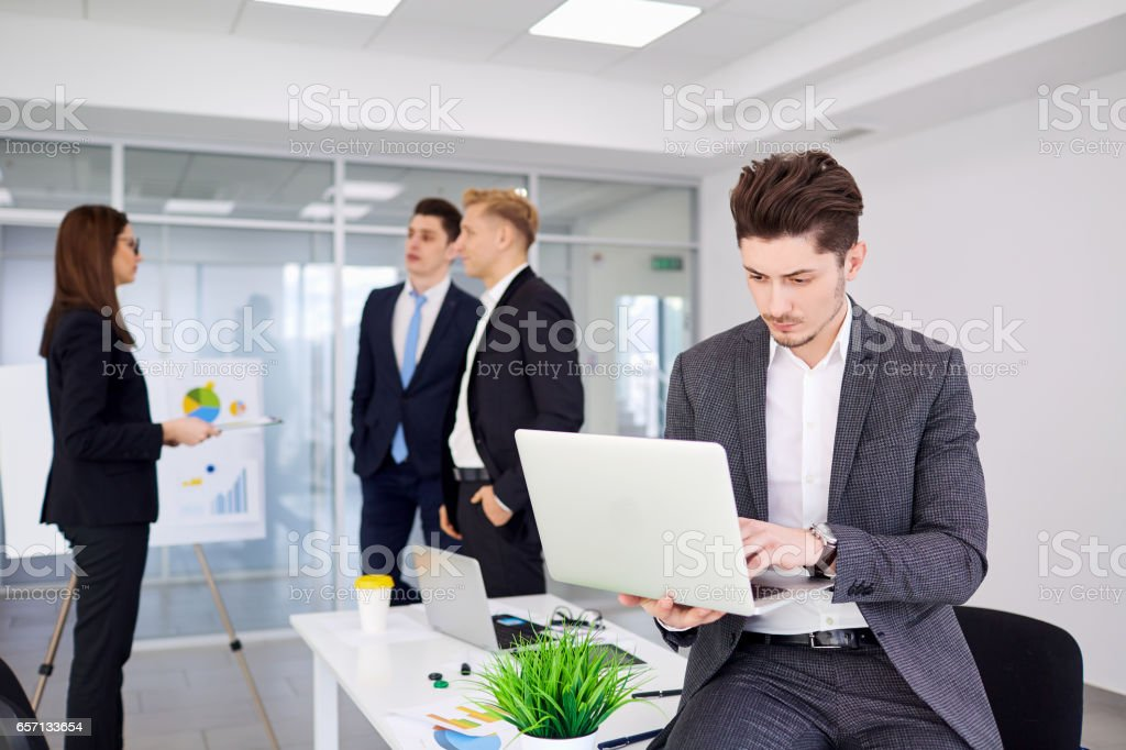 Businessman at his desk working on a laptop in the background bu stock photo