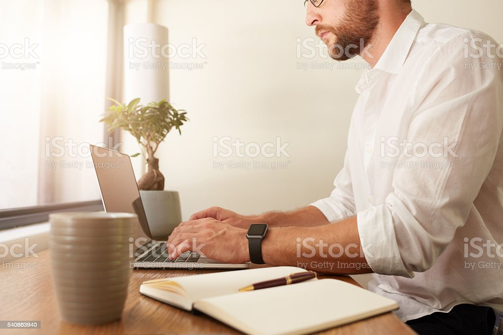 Businessman at home office working on laptop stock photo