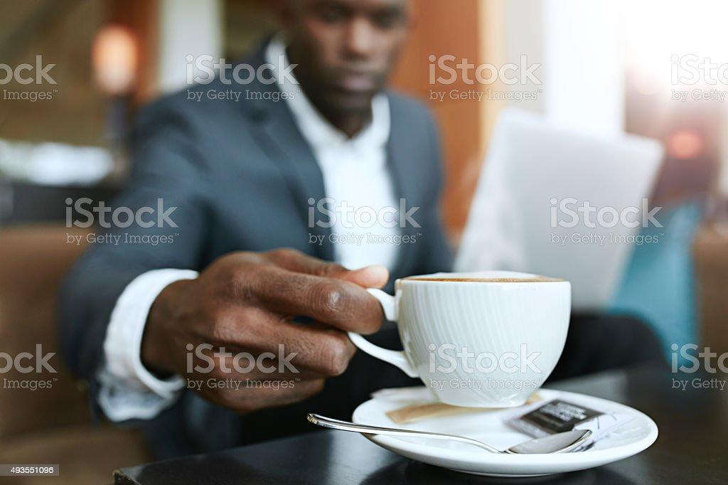 Businessman at hotel lobby drinking coffee stock photo