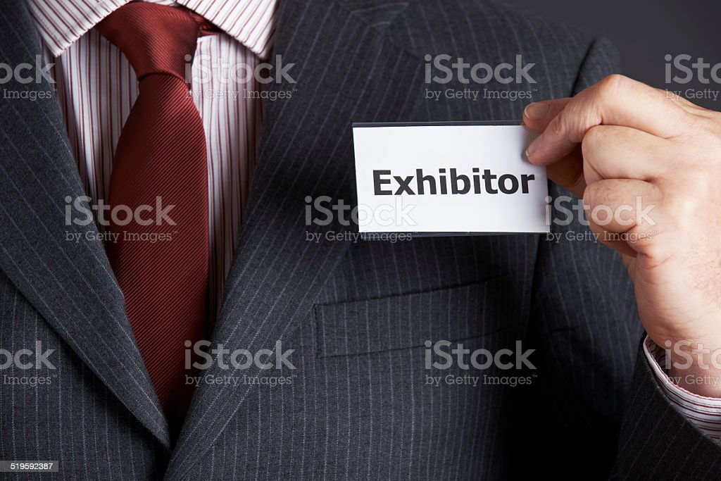 Businessman Attaching Exhibitor Badge To Jacket stock photo