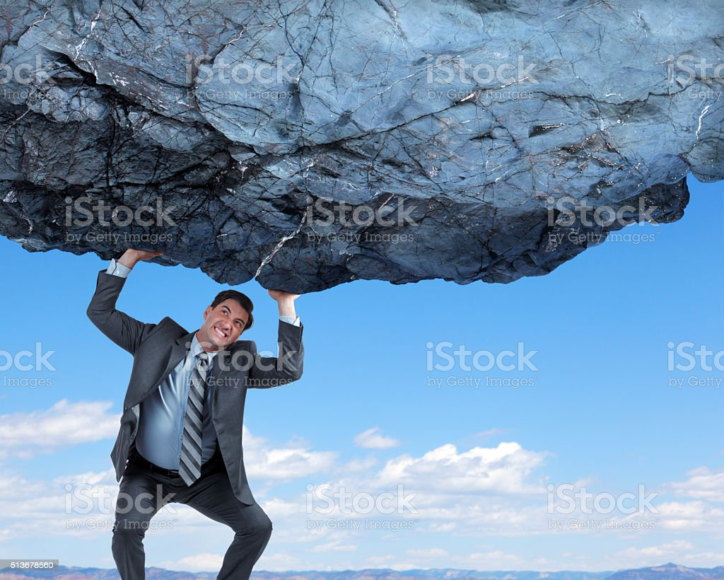 Businessman Attempting To Lift And Support Large Rock stock photo
