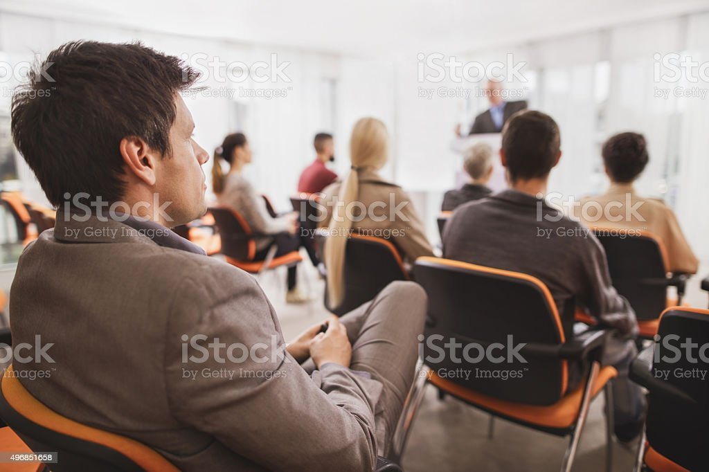 Businessman attending a business seminar at board room. stock photo