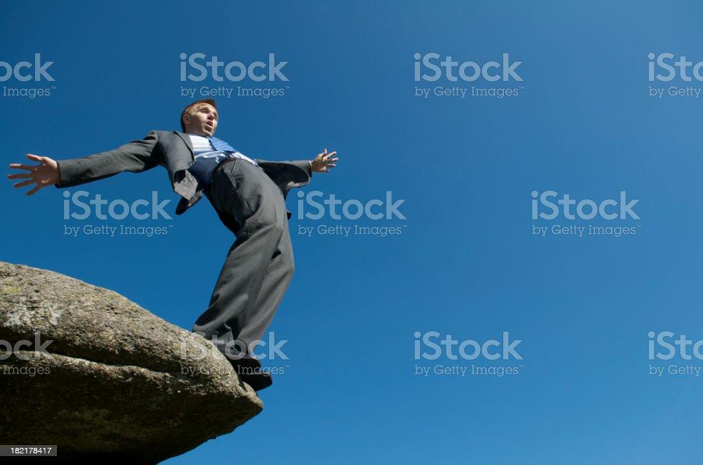 Businessman Balances at Edge of Cliff royalty-free stock photo