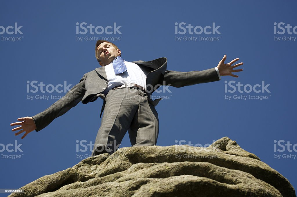 Businessman Balances at the Edge of Rock Cliff royalty-free stock photo