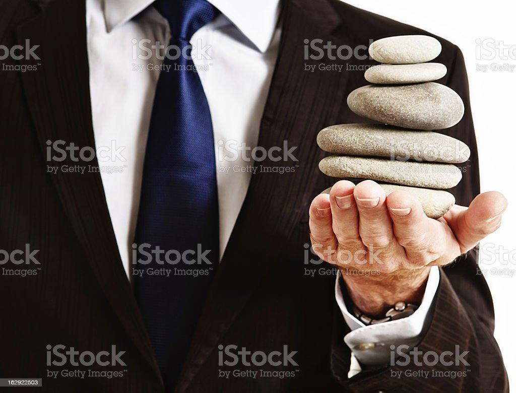 Businessman balances Zen rock stack in hand royalty-free stock photo