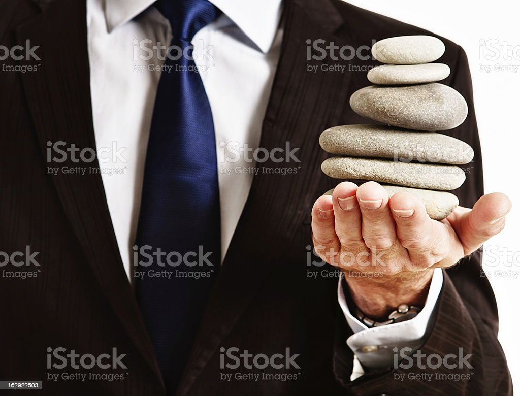 Businessman balances Zen rock stack in hand stock photo