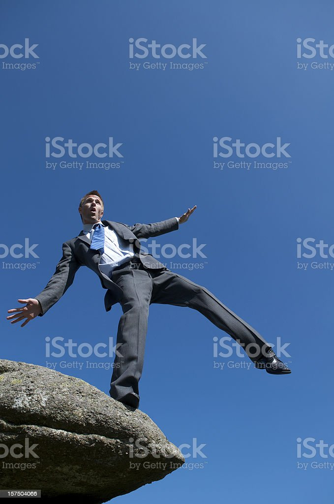 Businessman Balancing at Edge of Cliff Outdoors royalty-free stock photo