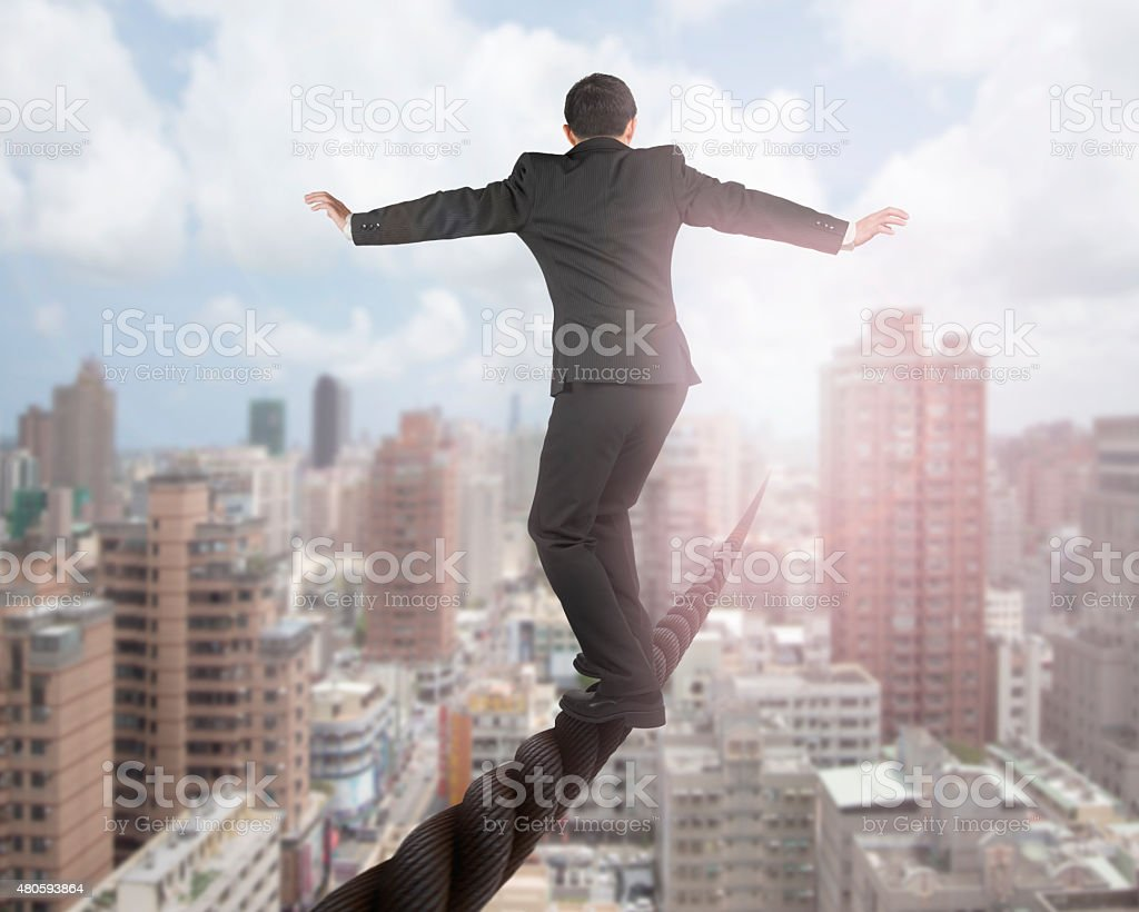 Businessman balancing on a wire with sky clouds cityscape stock photo