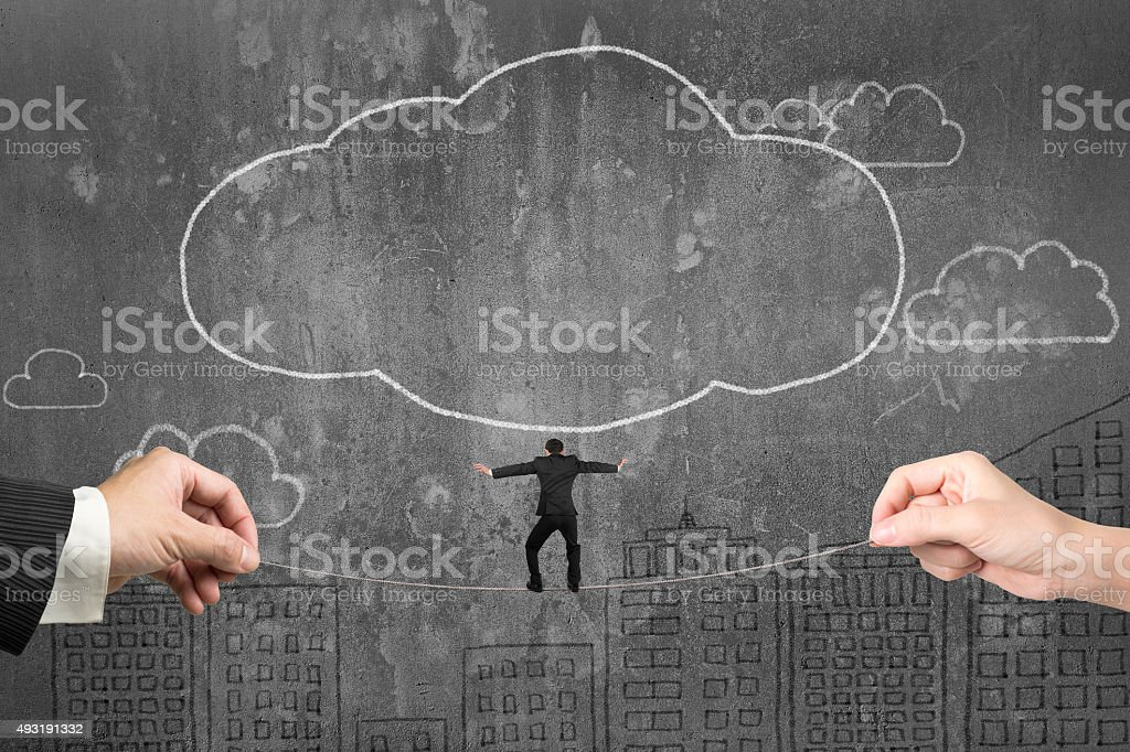 Businessman balancing on tightrope with male and female hands ho stock photo