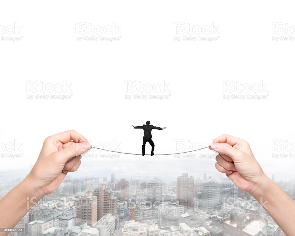 Businessman balancing on tightrope with woman two hands holding stock photo