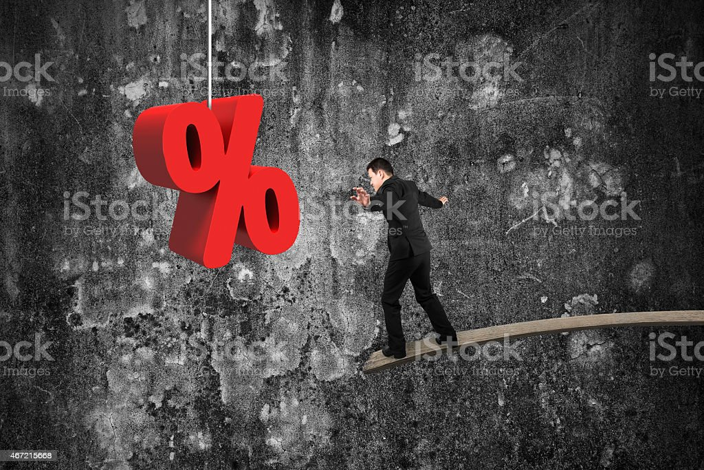 Businessman balancing on wooden board with red percentage sign stock photo