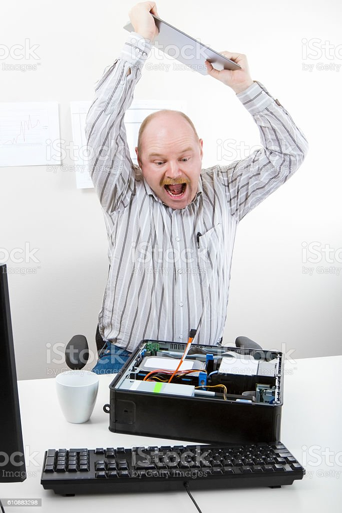 Businessman Banging File On Computer Chassis At Table stock photo