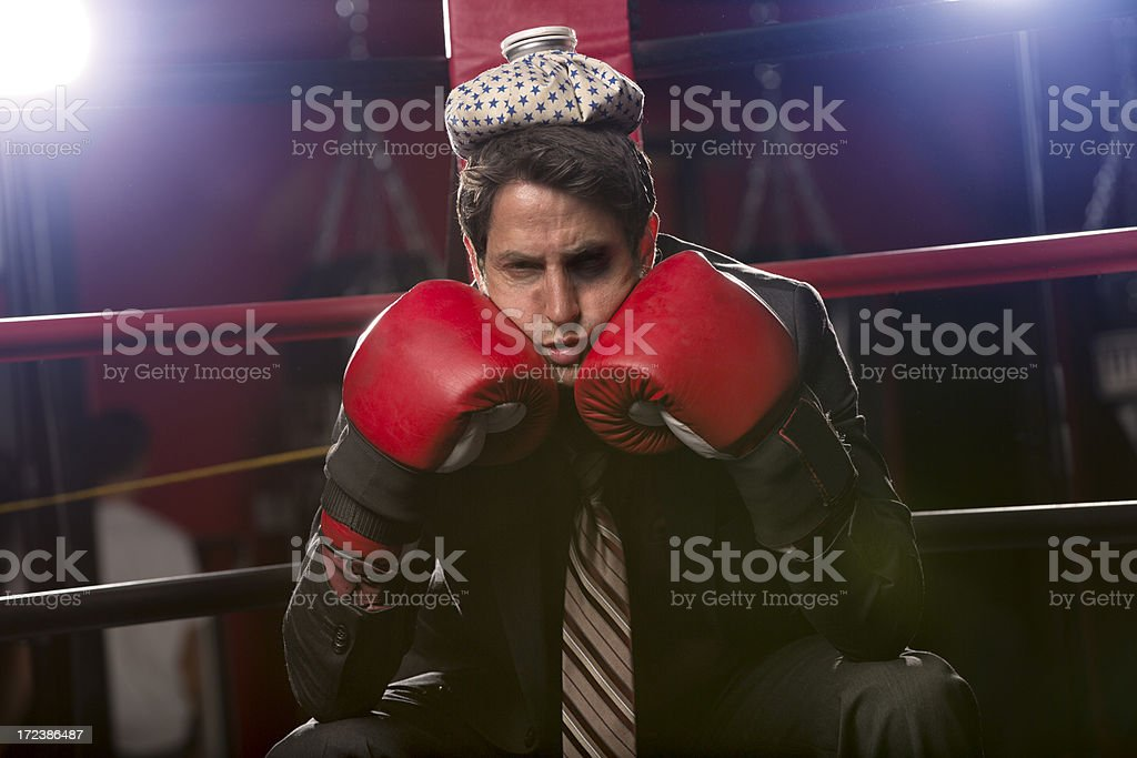 Businessman beat against the ropes with ice pack on head royalty-free stock photo