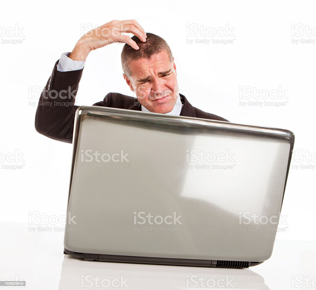 Businessman behind laptop scratches his head confused and frustrated stock photo