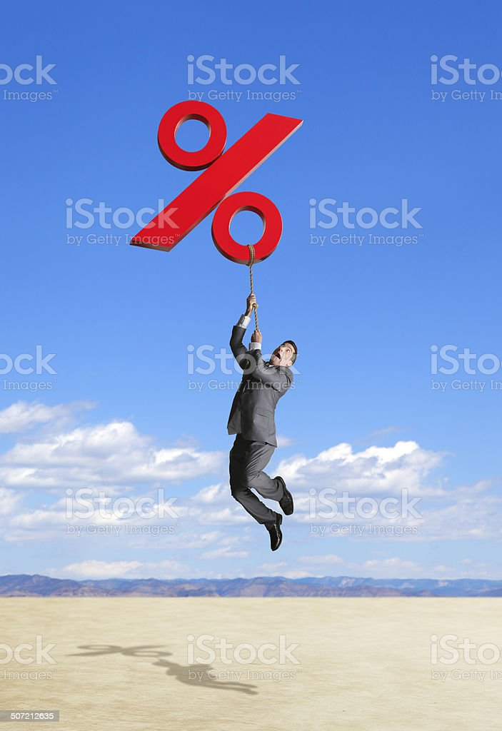 Businessman being lifted by rising interest rates stock photo