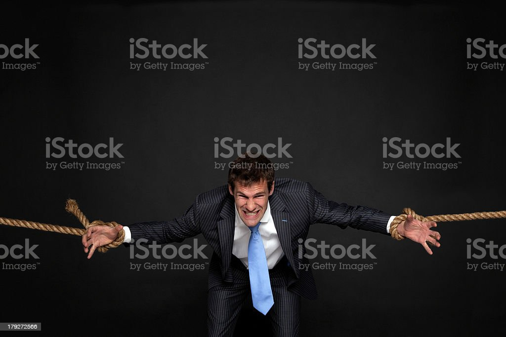 Businessman being pulled by rope on both sides. royalty-free stock photo