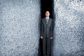Businessman Being Squeezed By Two Large Granite Rocks