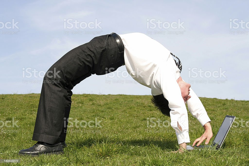 Businessman bending over backwards and using laptop stock photo