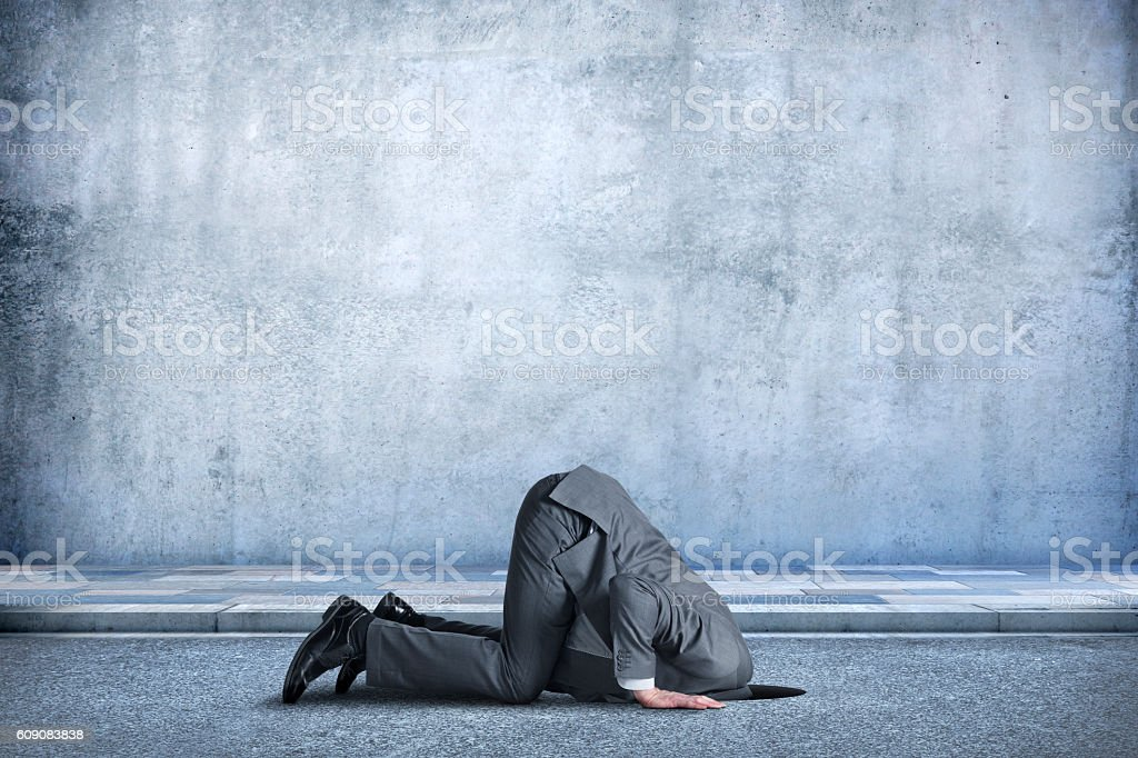 Businessman Bent Over With His Head In A Hole stock photo