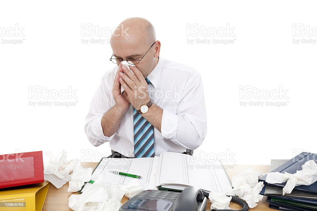 A businessman, blowing his nose, surrounded by used tissues royalty-free stock photo