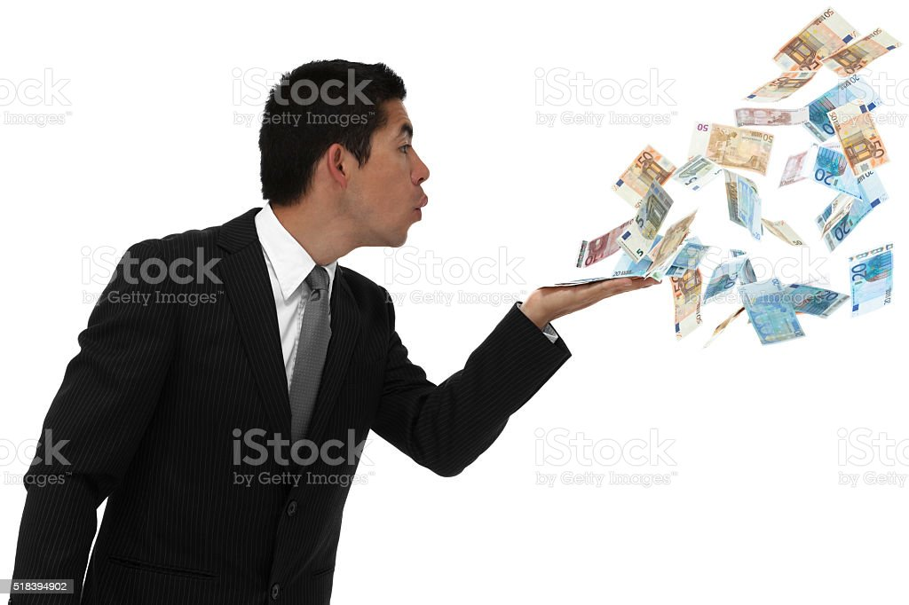 Businessman blowing money out of his hand stock photo