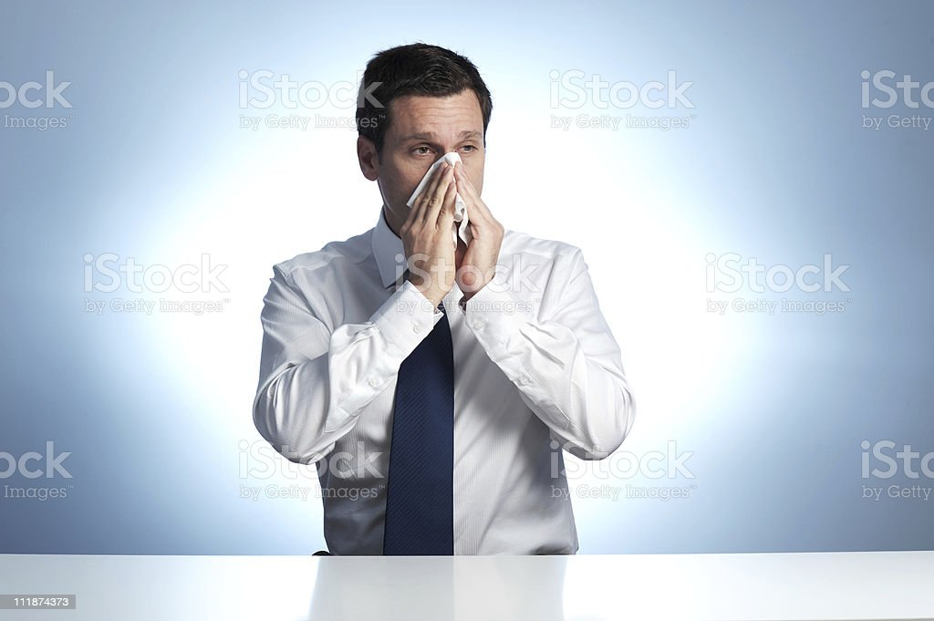 Businessman Blowing Nose on Blue Background royalty-free stock photo