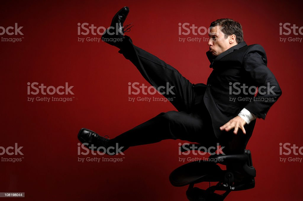 Businessman Blown Away in Office Chair on Red Background royalty-free stock photo